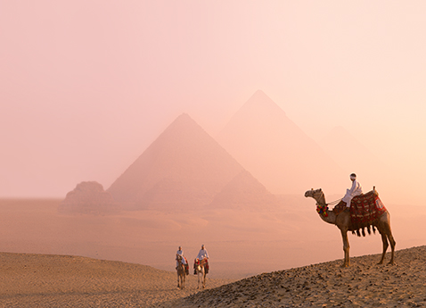 Three people riding camels with they pyramids of Giza, Egypt in the background