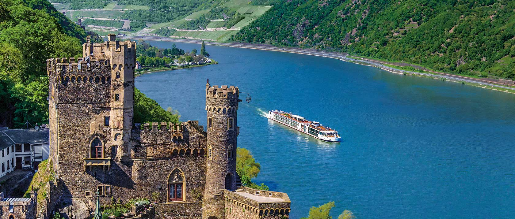 Aerial view of a Viking river ship sailing past Rheinstein Castle in Trechtingshausen, Germany