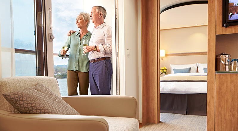 Elderly couple on the veranda of their stateroom looking towards the water