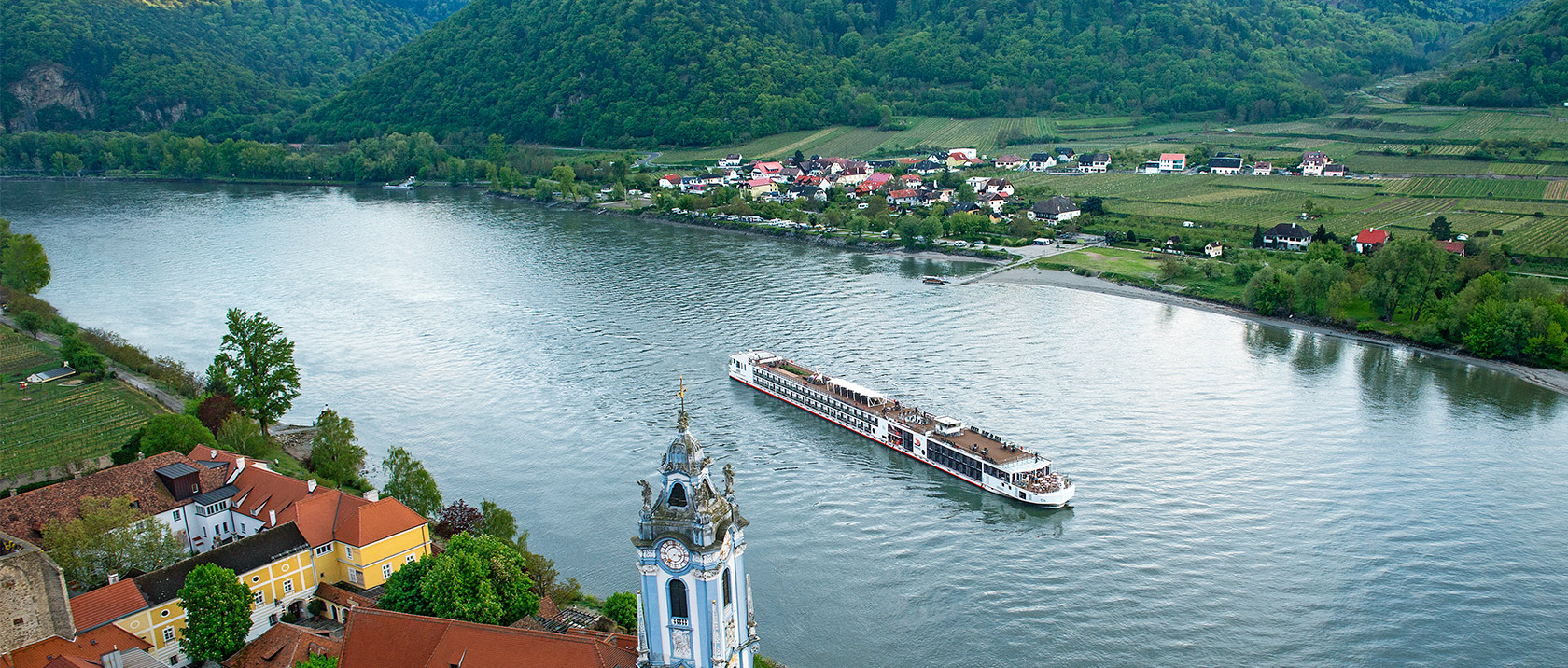 Aerial view of a Viking river ship sailing past Dürnstein, Austria along the Danube river