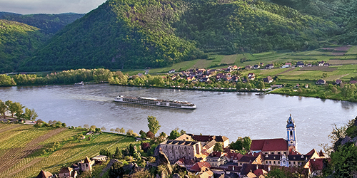 A Viking river ship sailing past a European town