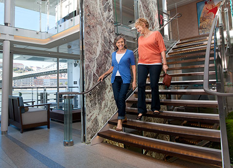 Two women walking down the stairs of the Atrium of a Viking river ship
