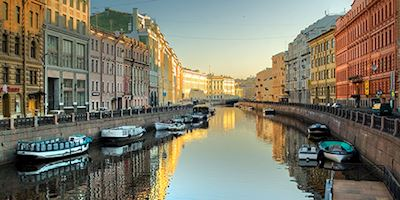A canal in St. Petersburg, lined with boats and colorful houses, sparkles in dawn light.