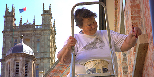 Pat the Painter up on a ladder, measuring and painting Highclere Castle.