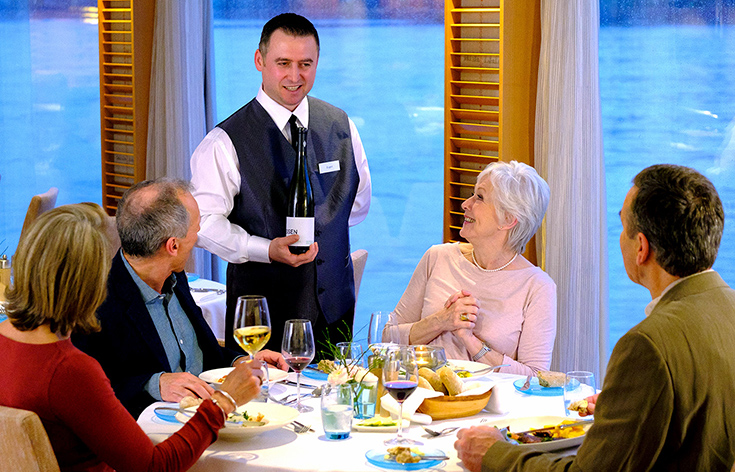 A Viking wine specialist speaking to four people at a dining table